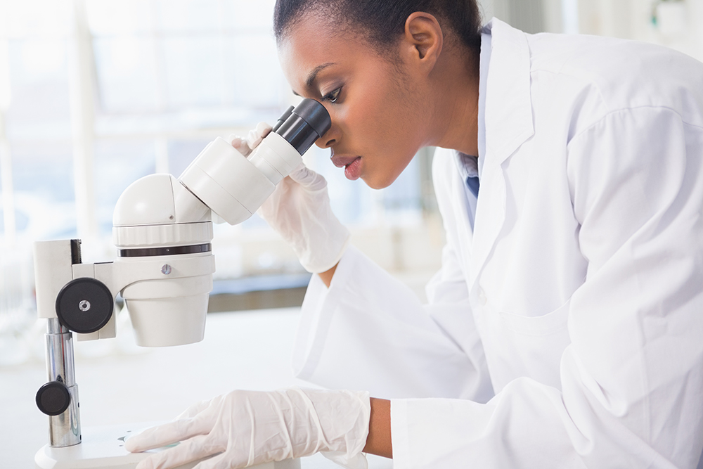 Bio-Pharma Lab Technician Looking Through a Microscope