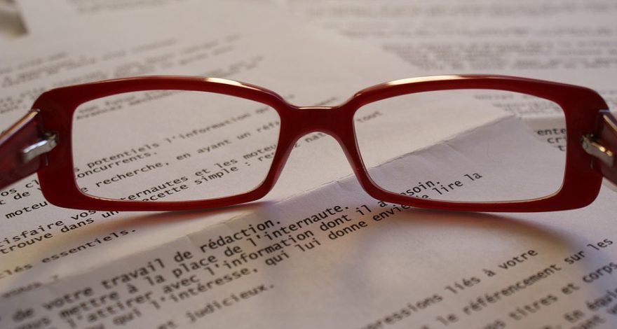 proofreader's glasses and documents to be proofed